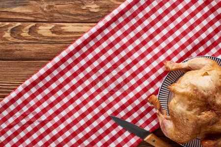 Photo for Top view of roasted turkey with knife served on red checkered napkin at wooden table for Thanksgiving dinner - Royalty Free Image