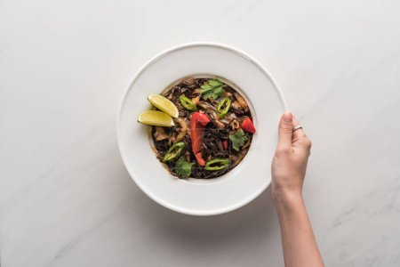cropped view of woman holding plate with delicious spicy thai noodles