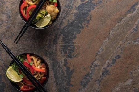 Photo pour Top view of delicious spicy thai noodles with chopsticks on stone surface - image libre de droit