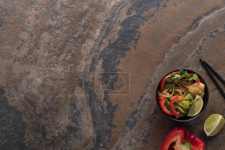 top view of tasty spicy thai noodles with chopsticks on stone surface