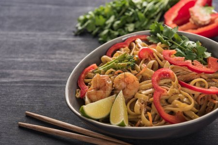 Photo for Delicious spicy thai noodles with shrimps near chopsticks on wooden grey surface - Royalty Free Image