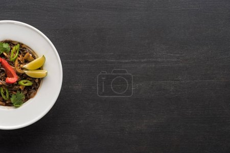 top view of tasty spicy thai noodles in plate on wooden grey surface