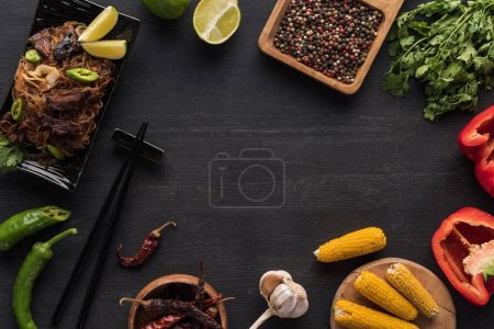 Photo for Top view of tasty spicy thai noodles near chopsticks and fresh ingredients on wooden grey surface - Royalty Free Image