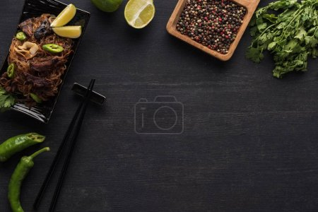 top view of tasty spicy thai noodles near chopsticks and fresh ingredients on wooden grey surface