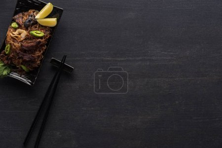 Photo for Top view of tasty spicy thai noodles near chopsticks on wooden grey surface - Royalty Free Image