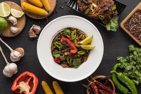 Photo for Top view of tasty spicy meat thai noodles near chopsticks and fresh ingredients on wooden grey surface - Royalty Free Image