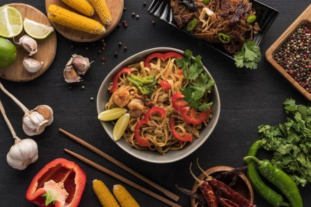 Photo for Top view of tasty spicy seafood thai noodles near chopsticks and fresh ingredients on wooden grey surface - Royalty Free Image