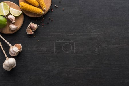 Photo for Top view of corn, garlic, peppercorn and lime on wooden grey surface with copy space - Royalty Free Image
