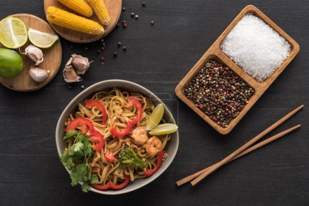 Photo for Top view of delicious spicy thai noodles with shrimps near chopsticks, seasoning, lime and corn on wooden grey surface - Royalty Free Image