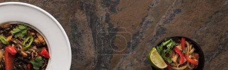 Draufsicht auf thailändische Nudeln und Essstäbchen auf Steinoberfläche, Panoramaaufnahme