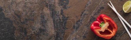 vista superior de pimiento y lima cerca de palillos en la superficie de piedra, plano panorámico