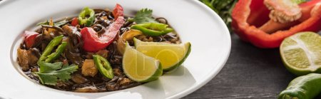 close up view of meat thai noodles near ingredients on wooden grey surface, panoramic shot