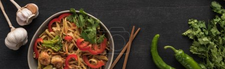 Photo for Top view of tasty spicy thai noodles with garlic, parsley, jalapenos near chopsticks on wooden grey surface, panoramic shot - Royalty Free Image