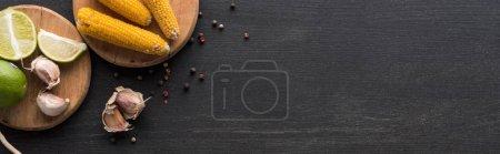 Draufsicht auf Mais, Knoblauch, Pfefferkorn und Limette auf hölzerner grauer Oberfläche mit Kopierraum, Panoramaaufnahme