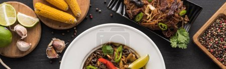 Photo for Top view of tasty spicy thai noodles near chopsticks and fresh ingredients on wooden grey surface, panoramic shot - Royalty Free Image