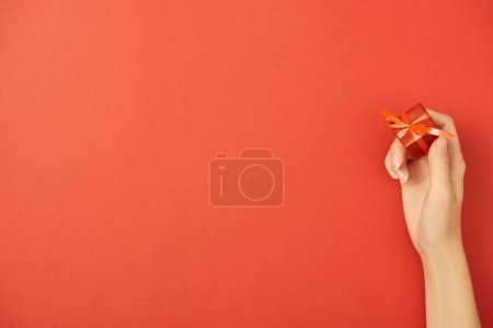 Photo for Cropped view of woman holding gift box on red background with copy space - Royalty Free Image