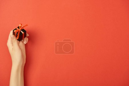 cropped view of woman holding black gift box on red background with copy space