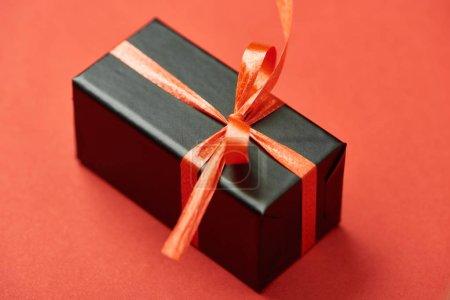 schwarze Geschenkbox mit Schleife und Schleife auf rotem Hintergrund
