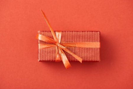 top view of gift box with bow and ribbon on red background
