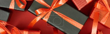 Photo for Top view of gift boxes with bows and ribbons on red background, panoramic shot - Royalty Free Image