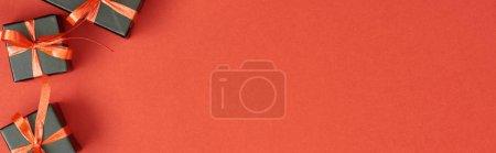 Photo pour Vue d'en haut de petites boîtes cadeaux noires sur fond rouge avec espace de copie, photo panoramique - image libre de droit