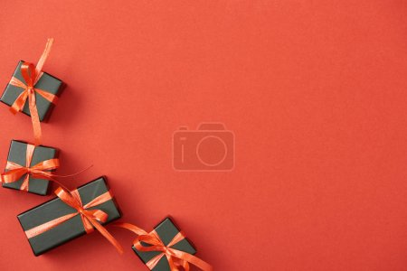 Photo for Top view of small black gift boxes on red background with copy space - Royalty Free Image