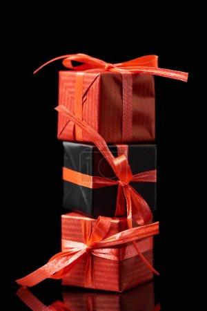 Photo pour Cadeaux décoratifs noirs et rouges isolés sur noir - image libre de droit