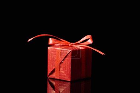 Photo pour Cadeau décoratif rouge isolé sur noir avec espace de copie - image libre de droit