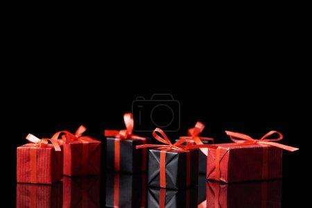Photo pour Cadeaux décoratifs noirs et rouges isolés sur noir avec espace de copie - image libre de droit