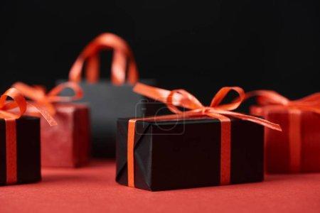 foyer sélectif de cadeaux avec rubans rouges et sac à provisions isolé sur noir