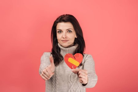 Photo for Woman in warm sweater holding paper cut with broken heart and band aid while showing thumb up on pink - Royalty Free Image