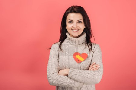 Photo for Cheerful woman with yellow band aid on heart-shaped paper cut standing with crossed arms on pink - Royalty Free Image
