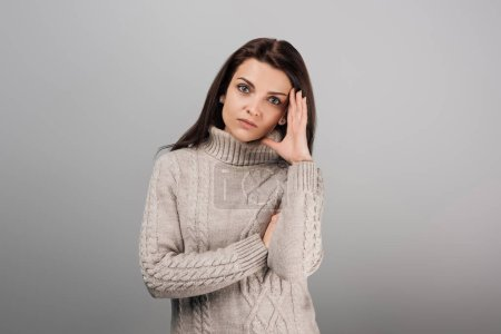 attractive woman with headache looking at camera isolated on grey
