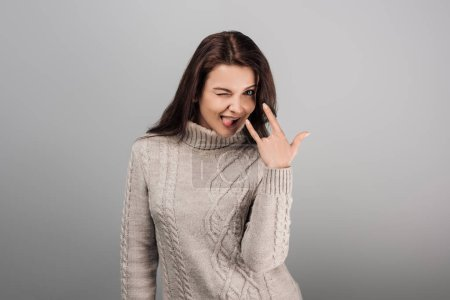 Photo for Cheerful woman showing rock sign while sticking out tongue isolated on grey - Royalty Free Image
