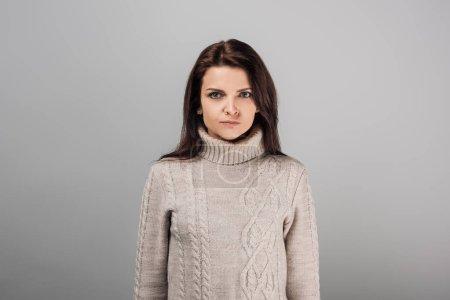 Photo pour Mécontente femme en chandail regardant une caméra isolée sur gris - image libre de droit