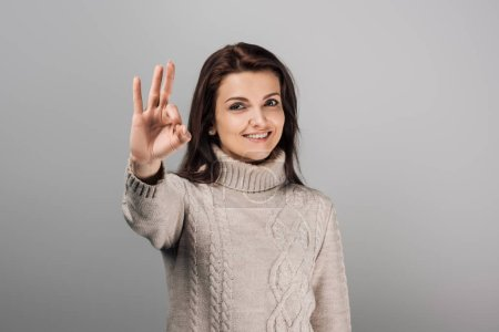 Foto de Alegre mujer en suéter mostrando ok signo aislado don gris - Imagen libre de derechos