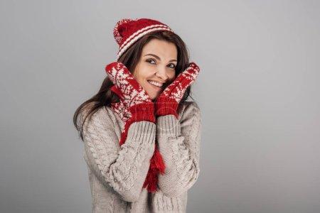 Photo pour Femme gaie en gants et chapeau tricoté touchant le visage isolée sur gris - image libre de droit