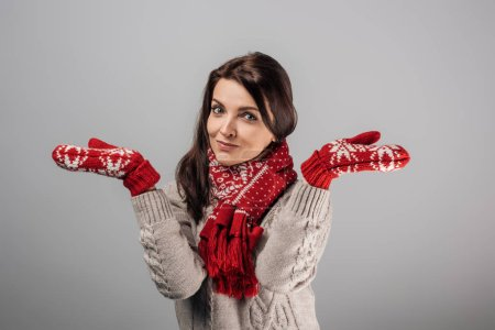 Photo for Woman in red gloves and scarf showing shrug gesture isolated on grey - Royalty Free Image