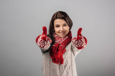 Photo for Happy woman in red gloves and scarf showing thumbs up isolated on grey - Royalty Free Image