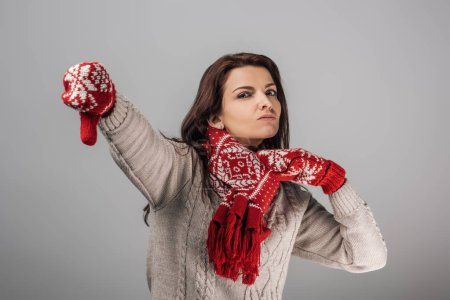 Photo for Dissatisfied woman in red gloves and scarf showing thumb down isolated on grey - Royalty Free Image