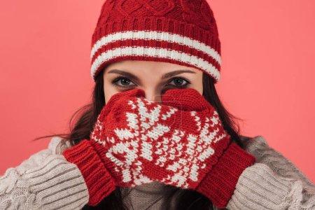 Photo pour Femme en bonneterie couvrant le visage avec des gants rouges et chauds isolés en rose - image libre de droit