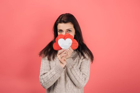 Photo for Woman in sweater covering face with heart-shaped paper artwork on pink - Royalty Free Image