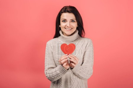 Photo for Happy woman in warm sweater holding paper cut with broken heart on pink - Royalty Free Image