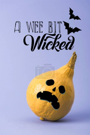 Photo for Yellow colorful painted pumpkin on violet background with a wee bit wicked illustration - Royalty Free Image
