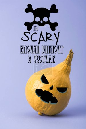 Photo pour Yellow colorful painted pumpkin on violet background with i am scary enough without a costume illustration - image libre de droit