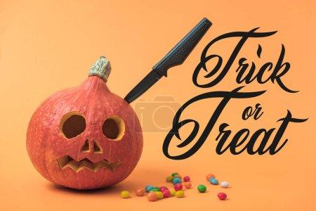Photo pour Fantasmagorique citrouille d'Halloween avec couteau et bonbons sur fond orange avec astuce ou traiter illustration - image libre de droit