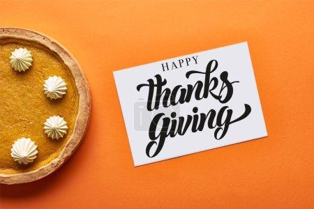 Photo pour Vue du dessus de tarte à la citrouille et carte avec illustration d'action de grâces heureuse sur fond orange - image libre de droit