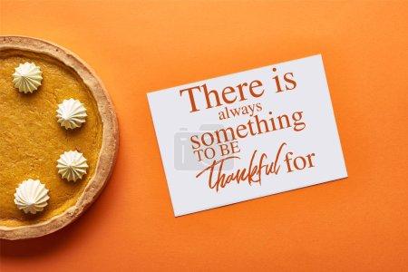 Photo pour Vue du dessus de tarte à la citrouille et la carte avec il ya toujours quelque chose à remercier pour l'illustration sur fond orange - image libre de droit