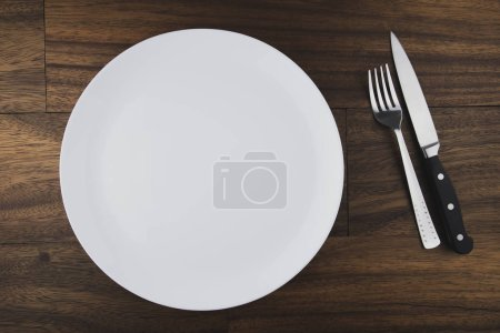 Photo for Top view of empty white food plate with fork and knife - Royalty Free Image