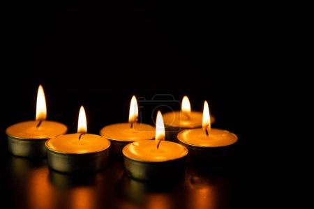 Photo pour Des bougies allumées sur fond foncé - image libre de droit